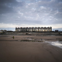Small houses under grey skies on seafront in England with young child on beach