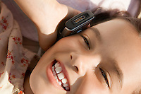 Girl lying down using mobile phone head and shoulders close up