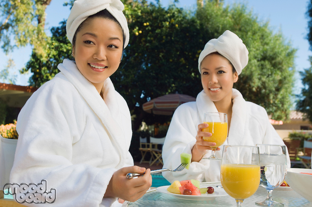 Two young women eating breakfast at outdoor table