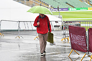 Rain Stops Play - A spectator walk around the ground with an umbrella up as the heavy rain continues to fall during the Specsavers County Champ Div 1 match between Somerset County Cricket Club and Essex County Cricket Club at the Cooper Associates County Ground, Taunton, United Kingdom on 23 September 2019.