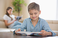 Cute boy reading book with mother in background at home