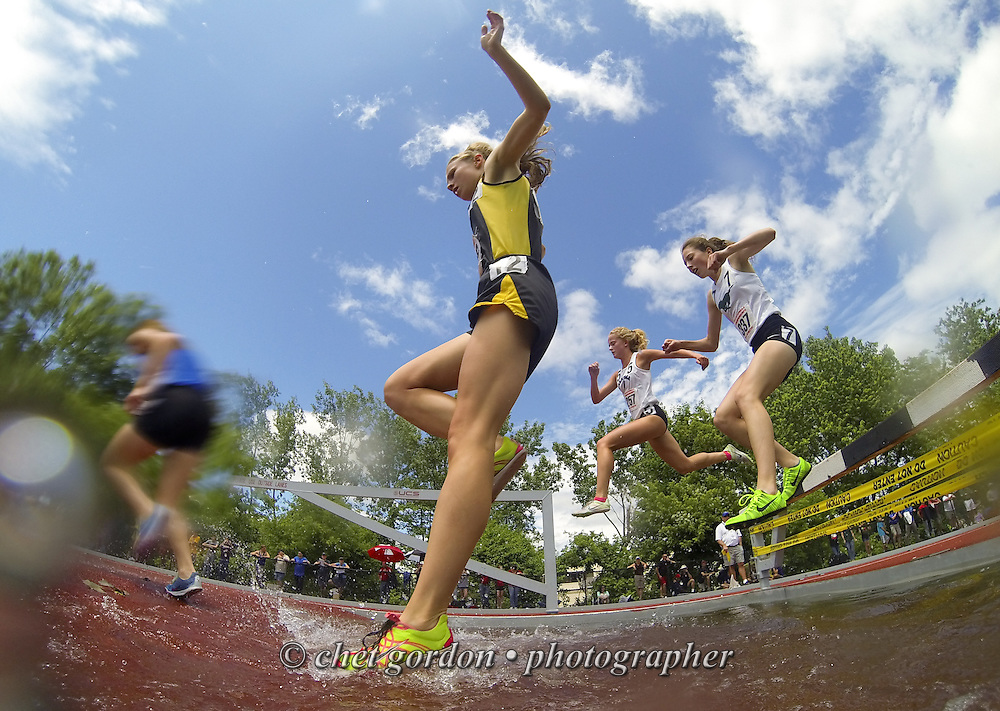 Runners clear the water obstacle during the Girls 2000 Meter Steeplechase at the NYSPHSAA Track and Field Championships at Faller Field in Middletown, NY on Saturday, June 8, 2013.