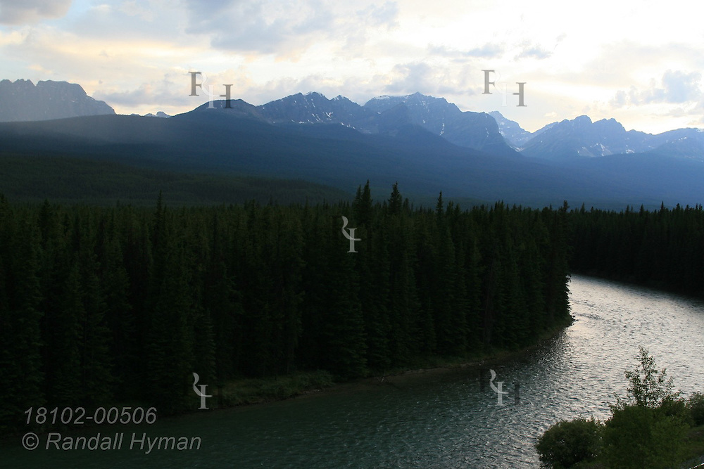Canadian Rockies soar in distance behind the Bow River in late evening on the Bow Valley Parkway in Banff National Park in the Candadian Rockies of Alberta, Canada.