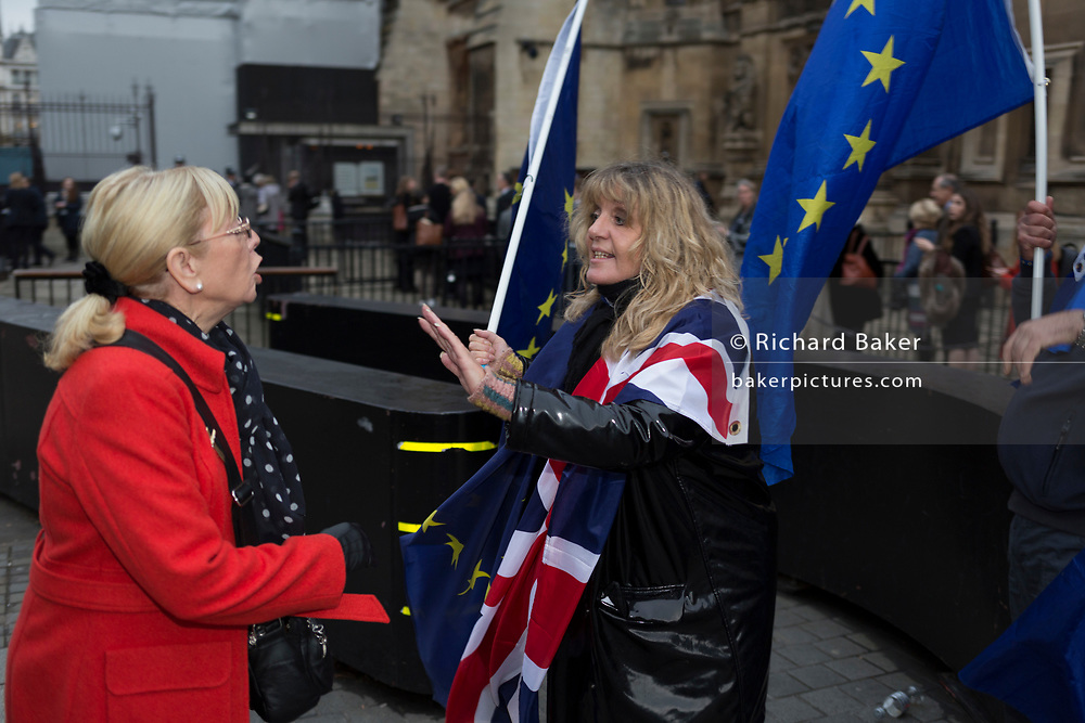 As MPs debate the timing of Brexit inside the House of Commons, a Brexiteer argues with a pro-Europe protester waves EU and Union Jack flags outside Parlament, on 15th November 2017, in Westminster, London, England.