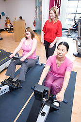 Fitness instructor watching  two women using the rowing machine at their sports leisure centre,