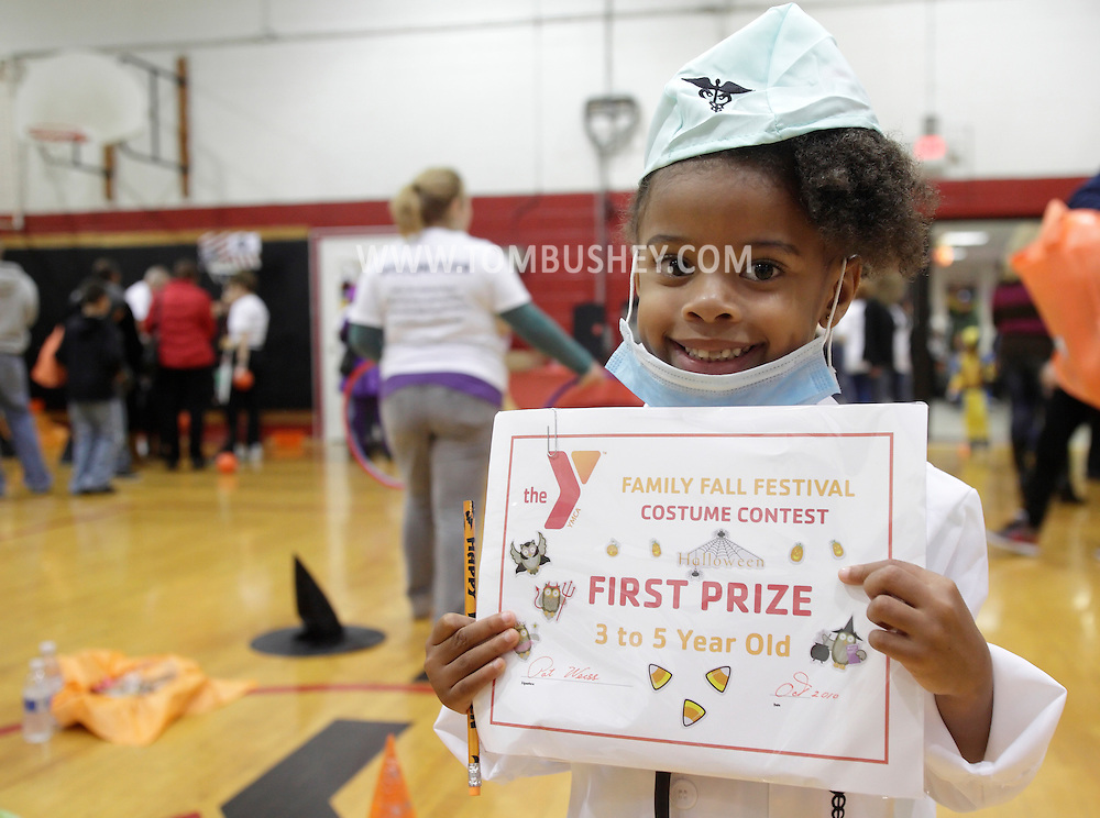 Middletown, New York - A little girl wearing a doctor's costume holds the prize she won at the Family Fall Festival at the Middletown YMCA on Oct. 23, 2010. ©Tom Bushey / The Image Works