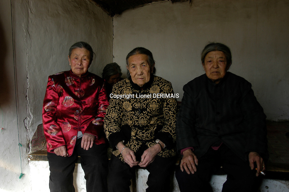 Meng Shujing (82)(L) with her two friends Yao Yun (82) (C) and Zhao Feng Lan (82) (R) also Manchu speakers in Sanjiazi near the town of Qiqihar in Heilongjiang province in North-east China photographed on March 3rd 2007..They are among the last Manchu speakers (less than 100 in the world).