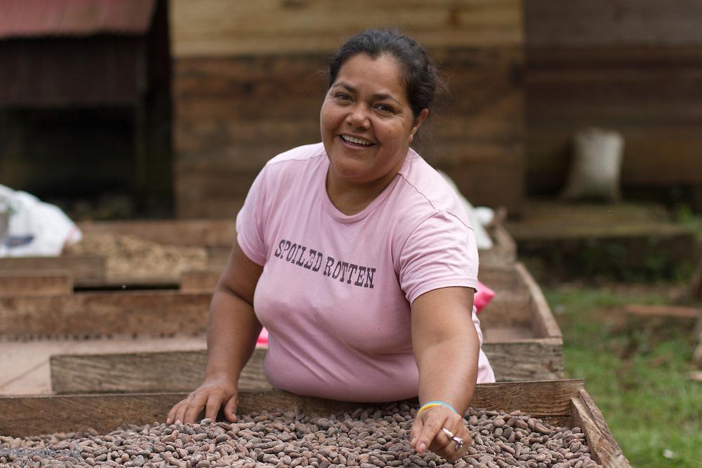 Natividad Miranda, 40, local cacao producer who manages ASIHERCA's fermentation and drying facility, checks drying cacao beans. ASIHERCA (Asociación de Iniciativas y Hermanamientos de El Castillo), a local association of small-scale producers, exports cacao certified by the Fairtrade Labeling Organization (FLO). Buena Vista, El Castillo, Río San Juan, Nicaragua. January 27, 2014.