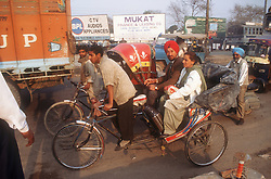 Bicycle rickshaw carrying middleclass couple stuck in traffic in Patiala; Punjab; India,