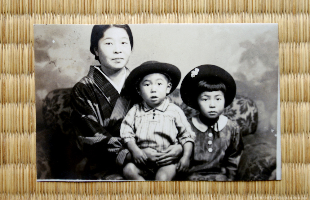 """Ms HIROKO KATAKEYAMA. Hiroshima A-Bomb survivor. Elementary school student who was four kilometers from the epicenter.  She lost many of her relatives in the bombing, including her cousin who was the same age.  We felt worn our and usually retreated to the barn, away from the quarreling adults.  One day my cousin confessed that his hair had started falling out.  I still vividly remember his blank face, frightened at this sign of death.  She still cries when she tells this story and is one of the few survivors who confesses to hating America. When she was invited by the UN to speak in New York two years ago, she almost didn't go. """"I couldn't bear the thought of going to the US"""". COPY: Old photo with her mother and her little brother who was kiled from the A-bombing of Hiroshima."""