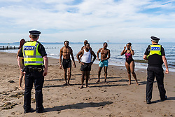 Portobello, Scotland, UK. 20 May 2020. Hot sunny weather brought out large crowds to Portobello beach today. Lockdown discipline seems to be a thing of the past with families and friends hitting the sand. A heavier than normal police presence had little visible effect since the public returned to the sand after the police walked away. Dancers from The Lion King UK Tour which was playing in Edinburgh before the lockdown are moved on by a police patrol.  Iain Masterton/Alamy Live News