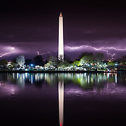Lightning stretches across the sky above the Washington Monument; reflecting in the waters off tidal basin near the Jefferson Memorial.