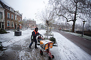 In Utrecht loopt een postbesteller dikt ingepakt zijn ronde door de sneeuw.<br /> <br /> In Utrecht a postman is walking in the snow.