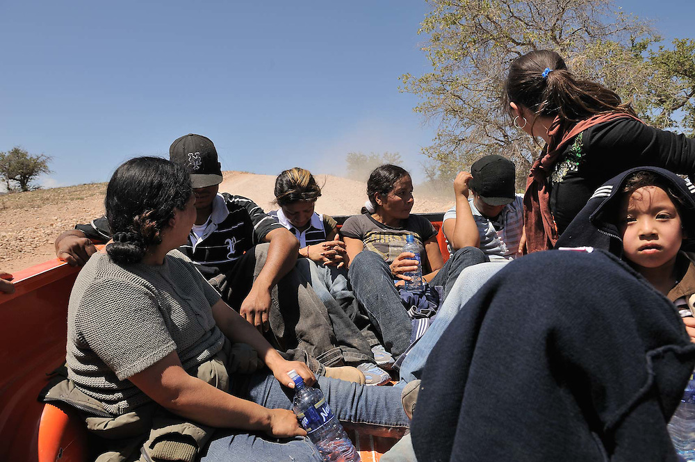 Mexican migrants, including women and young children, ride in the back of a Grupos Beta truck after being found wandering in the desert with no food or water near the Mexican city of Nogales.  Grupos Beta is a Mexican joint federal, state and municipally funded government organization whose role is to protect migrants from bandits, injury, illness or other perils while trying to enter the USA by walking across the desert for 3-4 days. As many as 2000 migrants a day, most from Mexico, cross the border illegally into the USA by going around, over, and through the fence between the two countries.  Referred to as illegal aliens by some in the USA.  Economic hardship drives many Mexicans, and other Central Americans, to risk their lives for a chance at a job in the United States. Immigration along the USA-Mexico border.
