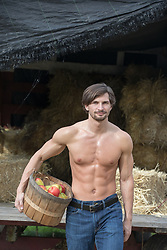 shirtless hunky man holding a basket filled with apples