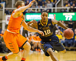 West Virginia Mountaineers guard Tarik Phillip (12) drives down the lane against the Oklahoma State Cowboys during the second half at the WVU Coliseum.