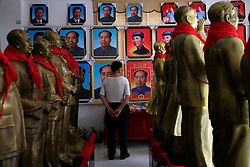 A visitor looks at portraits of Mao Zedong amid his statues on display at a wholesale souvenir store in Shaoshan, Hunan Province in central China, 28 April 2016. Shaoshan is the hometown of former Communist leader Mao Zedong, popularly known as Chairman Mao. Thousands of visitors descend on this small Chinese town burrowed in the hills of Central China's Hunan province to pay homage to the great helmsman everyday. It is one of the core sites of the 'Red Tourism' industry, where communist party cadres and ordinary Chinese tourists alike seek to relive the experiences and rekindle the spirit of the revolutionaries.