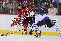 Jan 17; Newark, NJ, USA; New Jersey Devils left wing Ilya Kovalchuk (17) passes the puck while being defended by Winnipeg Jets defenseman Ron Hainsey (6) during the second period at the Prudential Center.