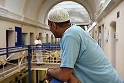 A Muslim inmate on the balcony outside his cell in Wandsworth prison..HMP Wandsworth in South West London was built in 1851 and is one of the largest prisons in Western Europe. It has a capacity of 1456 prisoners.