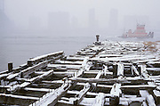 rundown pier with tugboat in background