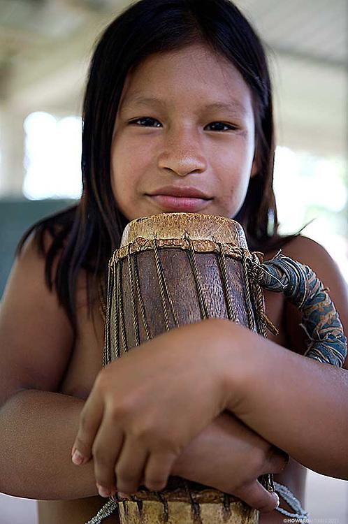 A young Embera girl cradles her drum, Darien Province, Panama.