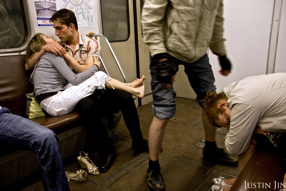 Youngsters kiss and collapse on the metro in Moscow, Russia. <br /> Picture by Justin Jin.