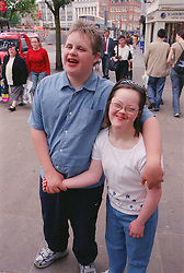 Teenage boy and girl with Downs Syndrome standing together in street holding hands,