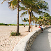 Miami, Florida - Couple Relaxing under Palm Trees in Lummus Park in South Beach