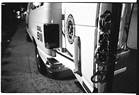 Handcuffs hang on the back of a paddy wagon during a drug raid.