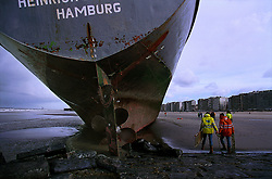 """BLANKENBERGE, BELGIUM - NOVEMBER 9, 2001 -  Workers from the salvage company Unie Van Redding - En Sleepdienst N.V. finish securing the damaged rudder on the German cargo ship """"Heinrich Behrmann"""", which was beached by heavy seas after losing power to the main engine late Thursday night at Blankenberge. The ship was heading for the port at Zeebrugge from Ireland, and was carrying dry cargo, none of which was hazardous. Unie Van Redding - En Sleepdienst N.V. was hired to free the ship. Three unsuccessful attempts were made Friday, the second attempt resulted in the injury of two workers when tug boat cables snapped. The beached ship has attracted the attention of curious tourists. (Photo © Jock Fistick)"""