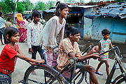 (left to right) Jyoti, 10, Poonam, 9, and Sachin, 17, sitting on his wheelchair, are playing around in Oriya Basti, one of the water-contaminated colonies in Bhopal, central India, near the abandoned Union Carbide (now DOW Chemical) industrial complex, site of the infamous '1984 Gas Disaster'.