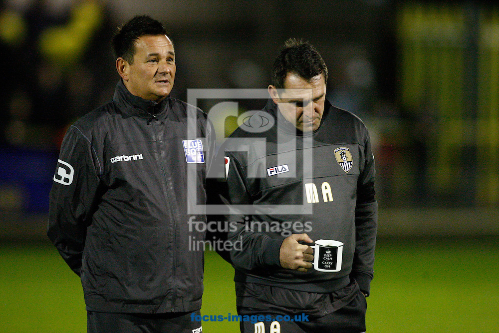 """Picture by Andrew Tobin/Focus Images Ltd. 07710 761829.. 4/12/11.  Paul Dodswell (L) of Sutton and Martin Allen, manager of Notts County (R) talk before the FA Cup 2nd round match between Sutton United and Notts County at The Borough Sports Ground, Surrey. Allen carries a tea mug labelled """"Keep Calm And Carry On""""."""