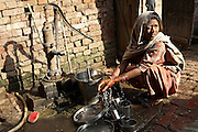 Sunita Kashap, 23, a housewife from the village of Bhanera Khemchand, pop. 2000, Saharanpur District, Uttar Pradesh, India, is portrayed while washing dishes near a hand-pump providing water contaminated with alarming levels of pesticides and heavy metals, on Wednesday, Mar. 26, 2008. Sunita is affected by a cancer on her right eye that has started to develop about two years ago. Doctors believe its cause to be the unsafe water she is drinking on an everyday basis.
