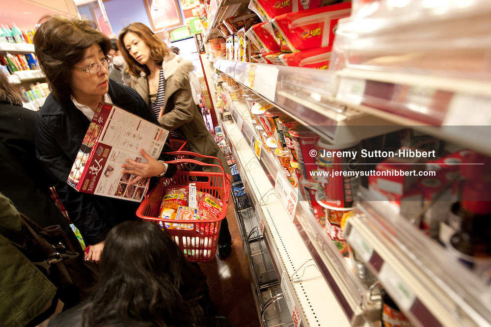 Shoppers enter a supermarket moments after it has opened, rushing in order to buy as much food as possible, as people fear food shortages in the days to come, on Monday morning in Kichijoji, Tokyo, Japan, on Monday 14th March 2011.
