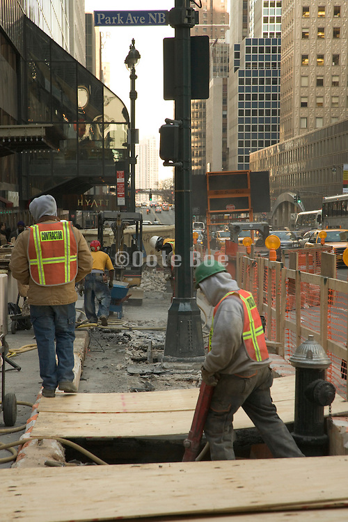 construction workers breaking up the street to make a repair New York City