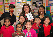 Elsa Simon, center, poses for a photograph with her students after receiving an iPad Mini from Houston ISD Human Resource representatives Sherelle Foust, left, and Patra Brannon, right, for winning a drawing from teachers who referred newly hired teachers at Janowski Elementary School, November 25, 2013.
