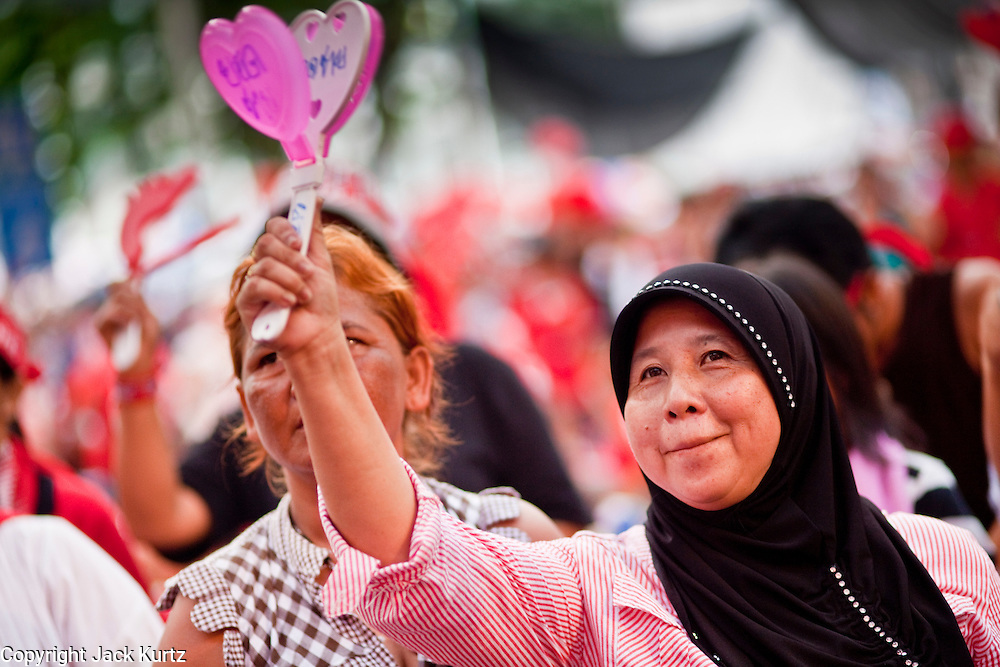 "May 3, 2010 - BANGKOK, THAILAND: Thai Muslim Red Shirt women dance and cheer while a Thai performer lip synchs the disco feminist song ""I Will Survive"" at the Red Shirt main stage in Ratchaprasong intersection Monday. The Red Shirt protests continued Monday amid rumors of a crackdown by authorities in the next 24 hours. Wednesday, May 5 is Coronation Day, which marks the day in 1950 that Thai King King Bhumibol Adulyadej assumed the throne as the King of Thailand.  The Red Shirts continue to call for Thai Prime Minister Abhisit Vejjajiva to step down and dissolve parliament and demand the return of ousted Prime Minister Thaksin Shinawatra.   PHOTO BY JACK KURTZ"