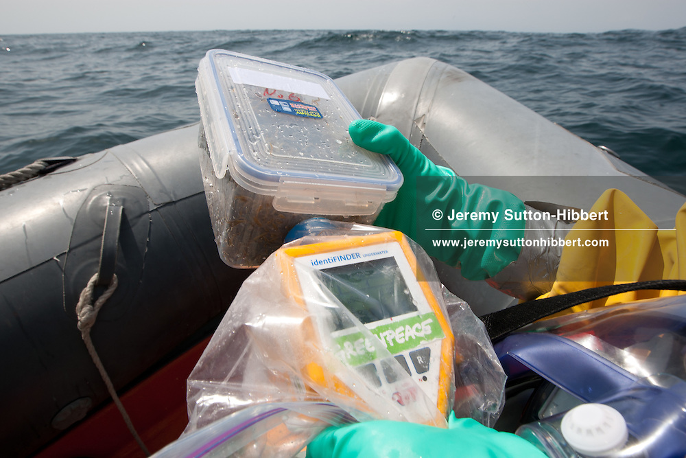 Crew from the Greenpeace ship Rainbow Warrior, including radiation safety advisor Jacob Namminga, collect sea water and seaweed samples to monitor for radiation contamination levels. As the Greenpeace ship sails up the eastern coast of Japan, in the vicinity of Fukushima, in Japan, Wednesday 4th May 2011..At coordinates 36' 50.807 North, 141' 14.306 East.