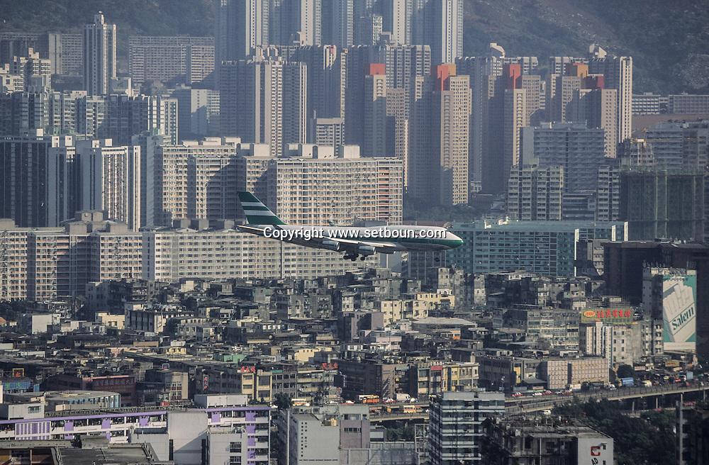 Hong Kong. planes landing on Kai tak airport in the center of the city over the buildings and the boats        / avion atterrissant en plein milieu de la ville sur aéroport  Kai Tak / Des avions au ras des buildings / Dans la ville de Hong-Kong surpeuplée, l'avion est le principal moyen d'accès à la ville. La seule piste d'atterrissage est en pleine ville       / R94/1    L1074  /  R00094  /  P0001911