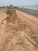 Rapid coastal erosion at East Lane, Bawdsey, Suffolk, England. Soft crag cliffs are easily eroded, dark underlying London clay is exposed. The second world war pill box indicates where the coast was around ten years ago. The historic martello tower has been defended from erosion by rock armour imported from Scandinavia.