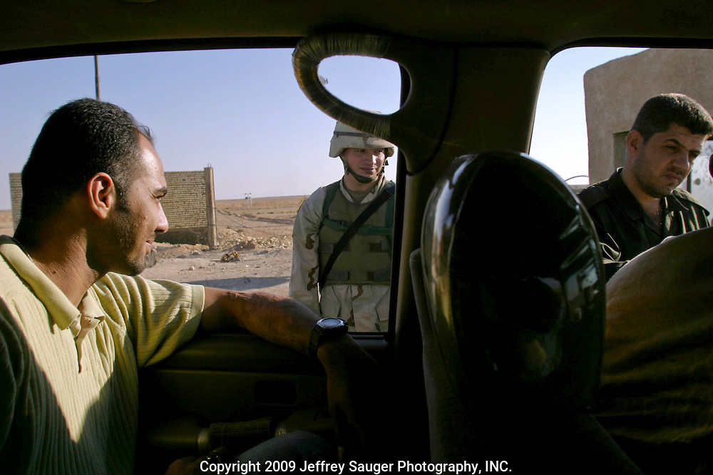 Emad Al-Kasid, left, smiles in amazement and disbelief, as a U.S. soldier watches an Iraqi border patrol officer/translator check the Al-kasid family's visas in Al Quim, Iraq, as the family finally clears the Syrian-Iraqi border at about 8:30a.m. Sunday, July 20, 2003. The family is returning to its home city of Nassiriyah, Iraq, for the first time since 1991 after fighting in the failed uprising against Saddam Hussein, fleeing to a refuge camp in Saudi Arabia for 3 years and finally settling in Dearborn, MI.
