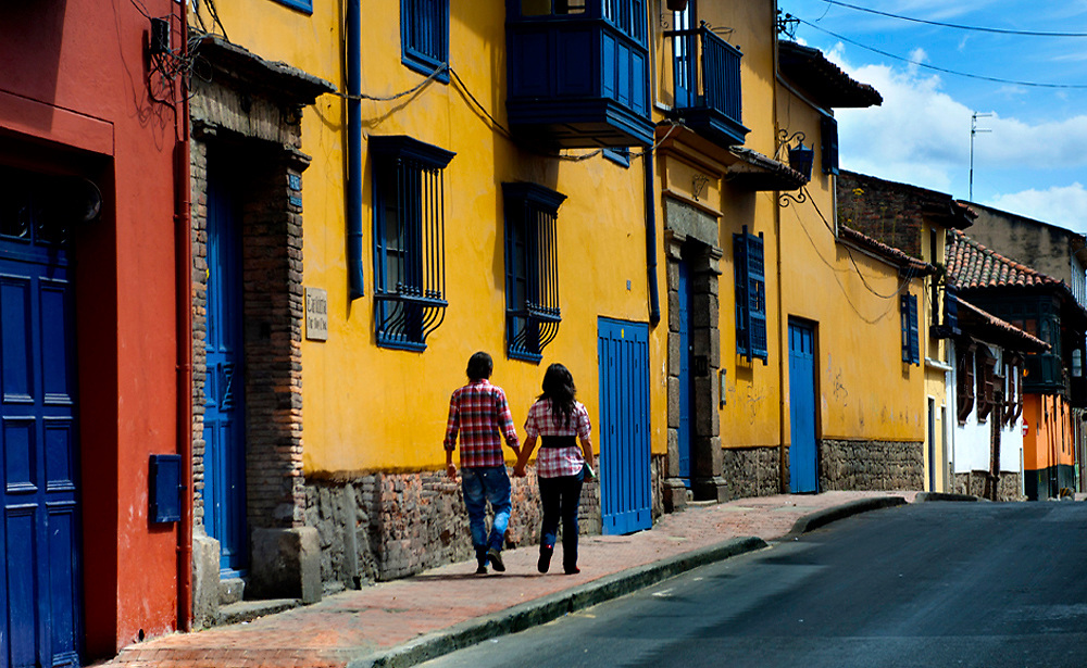 Couple walk by the coloful houses in the historic La Candaleria district of Bogota, Colombia