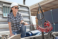 Mid adult woman holding a break hose of a flatbed truck