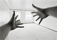 Out of focus hands reaching across an empty room toward brightly lit windows. Black and White.<br />