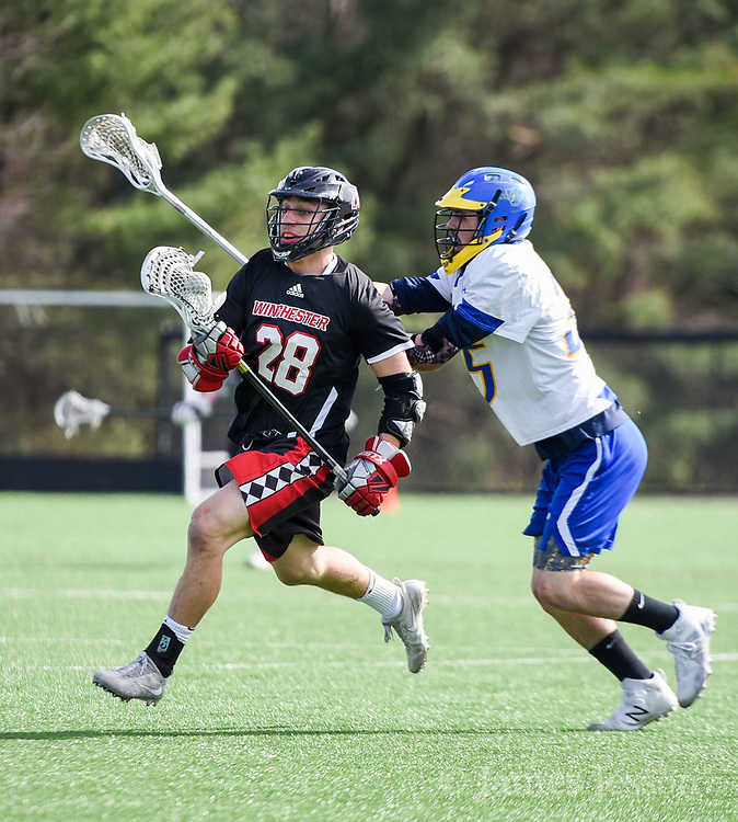 Winchester High School senior Peter Gallagher moves the ball up the field under pressure from Lexington High School senior Ryan Blanchard   during the game in Lexington, April 24, 2018. Winchester won the game, 11-6.   [Wicked Local Photo/James Jesson]
