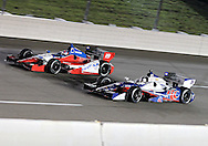 Marco Andretti (26) and James Jakes (19) race side by side during the IZOD IndyCar Iowa Corn Indy 250 auto race at the Iowa Speedway in Newton, Iowa on Saturday, June 23, 2012.