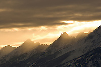 A setting sun illuminates low clouds over the Tetons in Grand Teton National Park, Jackson Hole, Wyoming.