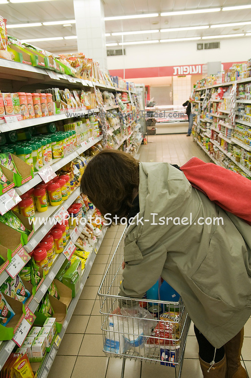 Woman filling her cart with products in a supermarket Model Release Available