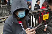 A visitor to the capital wearing a face mask against poor air quality uses her mobile phone in Piccadilly Circus, on 16th April 2018, in London, England.