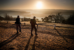 © Licensed to London News Pictures. 05/01/2017. Chilworth UK.  Walkers on St Martha's Hill on the North Downs enjoy the view at sunrise.  A continuing cold spell has seen temperatures as low as -6 in some areas. Photo credit: Peter Macdiarmid/LNP